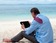 Business man working on the beach with tablet computer